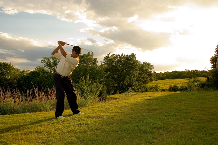 An outdoor sports photo of a golfer at the end of his swing. He is looking toward the setting sun and has scenic green grass, trees and satiny clouds around him.